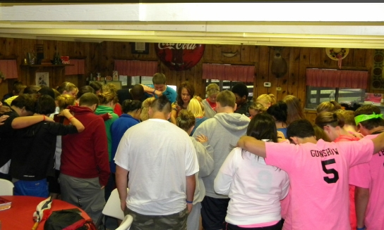 Candise (center) huddled up with students, praying for power to influence their public schools for Christ